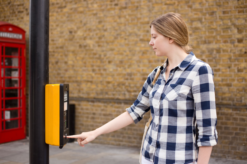 DVSA Syllabus lady pressing button at a crossing