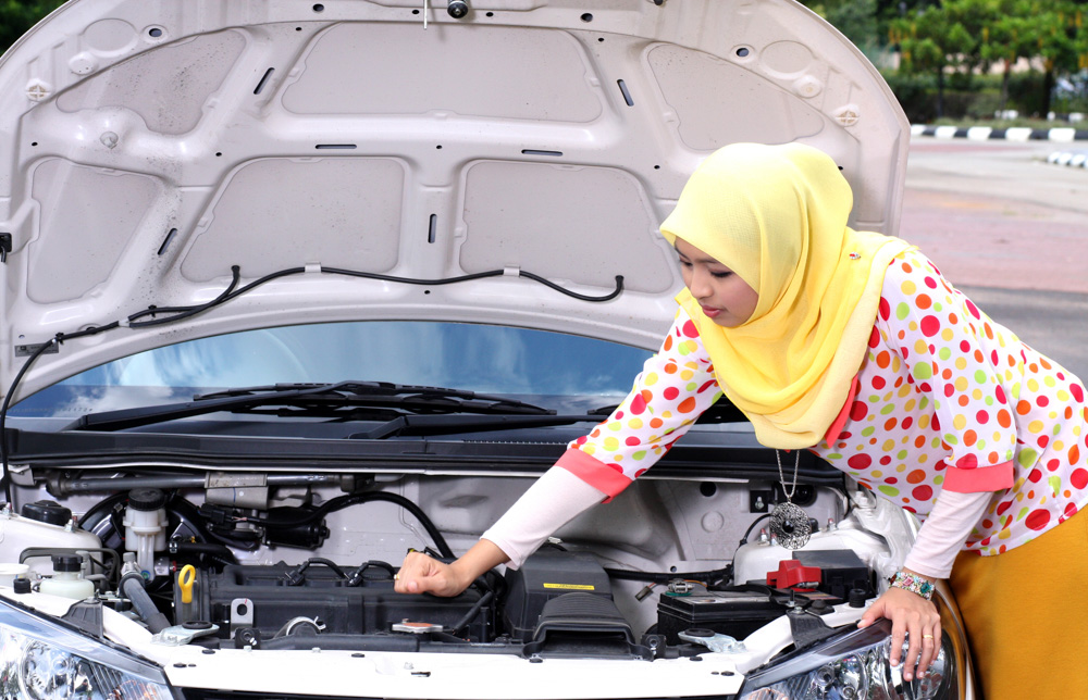 Lady checking under the bonnet